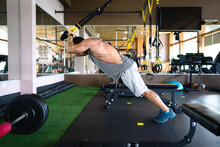 Side View Of Athletic Male In Sportswear Doing Exercises On TRX Straps During Suspension Training In Modern Gym
