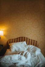 Hotel Room Interior With Crumpled Sheet And Blanket On Bed Against Ornamental Wall And Glowing Lamp