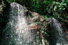 Picturesque View Of Cascade With Water Fluid Near Pond And Bright Green Shrubs In Sunlight