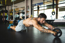 Side View Of Focused Muscular Male Athlete Doing Abs Exercises On Wheel During Intense Workout In Gym