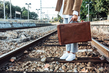 Crop Unrecognizable Female Traveler With Vintage Leather Suitcase Standing On Rails At Railway Station