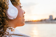 Side View Of Cropped Cheerful Black Female In Wireless Headphones Enjoying Music On Seashore In Evening