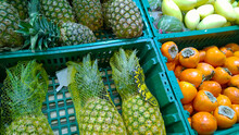 Pineapple And Persimmon In Boxes On Supermarket Shelves. Fresh Fruits At Farmers Market Stall. Retail Industry. Discount. Grocery Shopping. Healthy Eating. Farm Stand. Organic Exotic Food. Chain Store