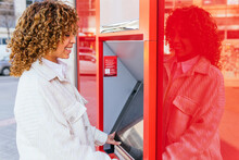 Side View Of Smiling African American Female Using ATM Terminal And Withdrawing Cash While Standing On City Street