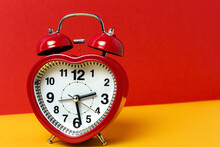 Red Metal Alarm Clock In Shape Of Heart Placed On Vibrant Two Colored Background In Studio