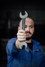 Male Mechanic In Blue Overall Covering Face With Metal Spanner In Hands Looking Away On Black Background