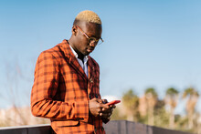 Ethnic African American Male With Hair Dyed Blond In Stylish Suit And Wristwatch Browsing On Cellphone While Standing In The City