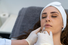 From Above Of Crop Unrecognizable Professional Beautician With Syringe Injecting Filler With Hyaluronic Acid In Lips Of Female Client During Procedure In Beauty Clinic