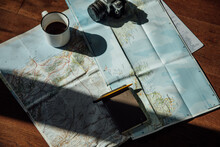 Top View Of Vintage Photo Camera And Metal Mug Of Coffee On Route Map During Trip