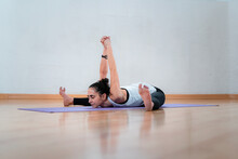 Ground Level Of Mature Female With Closed Eyes And Raised Arms Practicing Yoga On Mat In Room