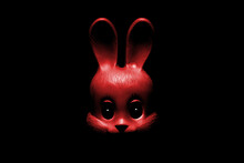 The Face Of A Red Toy Rabbit In The Dark