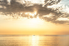 Remote View Of Boat Floating On Rippling Water Of Calm Sea On Background Of Bright Sundown Sky