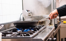 Side View Of Crop Unrecognizable Cook Preparing Dish In Frying Pan On Stove In Kitchen Of Restaurant