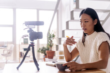 Young Ethnic Female Vlogger With Notebook Sitting At Table With Photo Camera On Tripod In Kitchen
