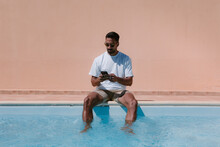 Serious Male Freelancer Sitting At Poolside With Legs In Water And Speaking On Mobile Phone During Remote Work In Summer