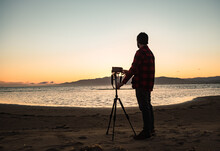Side View Full Body Of Unrecognizable Male Photographer Standing Near Tripod With Photo Camera And Preparing For Shooting Seascape At Sundown Time