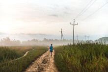 Back View Of Unrecognizable Male Runner Jogging Along Sandy Path In Countryside During Training In Foggy Morning In Summer