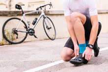 Crop Unrecognizable Male Bicyclist In Sports Clothes And Modern Cycling Shoes Squatting On Roadway Against Bike