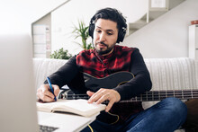 Adult Male Guitarist In Headphones With Electric Guitar Taking Notes In Notebook While Composing Music Against Netbook On Sofa At Home