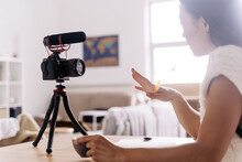 Side View Of Young Ethnic Female Vlogger With Notebook Sitting At Table With Photo Camera On Tripod In Kitchen