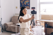 Serious Ethnic Female Vlogger Recording Video On Photo Camera While Standing In Living Room