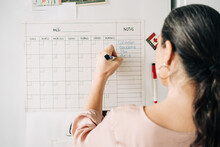 Back View Of Anonymous Female Taking Notes In Calendar On Fridge With Magnets While Making Plans In Kitchen At Home