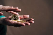 Crop Unrecognizable Dealer With Metal Crypto Coins With Letter And Ornament On Golden Surface