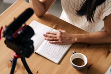 Cropped Unrecognizable Female Vlogger With Notebook Sitting At Table With Photo Camera On Tripod In Kitchen