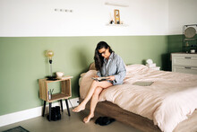 Full Body Of Concentrated Barefooted Middle Aged Ethnic Woman In Casual Clothes And Eyeglasses Sitting In Bed And Reading Interesting Novel At Home