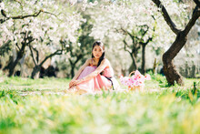 Peaceful Asian Woman In Pink Dress Sitting On Plaid With Blooming Flowers In Wicker Basket In Lush Garden And Looking At Camera