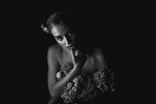 High Angle Black And White Of Charming Young Bare Shouldered Female With Bunch Of Flowers And Floral Adornment On Head Touching Lips And Looking At Camera In Dark Studio