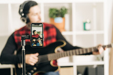 Tripod With Cellphone Screen Representing Photography Of Male Musician In Headset Playing Bass Guitar In House