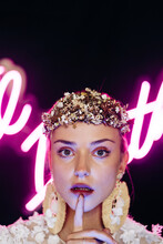Charming Tender Young Bride In White Lace Gown And Luxurious Floral Wreath And Earrings Looking At Camera Against Black Background With Neon Lights