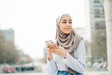 Young Ethnic Female In Hijab Standing In City And Messaging On Mobile Phone