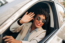 Cheerful African American Female In Stylish Sunglasses And Fashionable Outfit Smiling And Waving Hand In Automobile