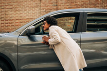 Side View Of Cheerful African American Female Smiling And Looking At Mirror Of Modern Silver Car Near Brick Building