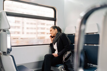 Side View Of Content Female Sitting On Passenger Seat And Looking Out Window While Having Phone Call In Modern Train