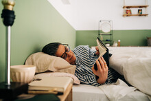 Relaxed Mature Hispanic Woman In Casual Clothes And Eyeglasses Lying In Bed And Reading Interesting Book Before Sleeping