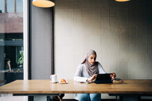 Content Muslim Female In Hijab And Talking On Video Chat Via Tablet While Sitting At Table In Cafe