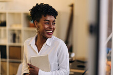 Cheerful African American Female Entrepreneur In White Shirt Standing In Room And Holding Notepad While Working Form Home And Looking Away