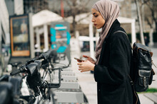 Side View Of Muslim Female In Headscarf Using Bicycle Sharing System In City