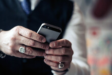 Crop Unrecognizable Male Executive In Rings Text Messaging On Mobile Phone On Blurred Background