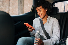 Cheerful Young African American Female In Striped Shirt Browsing Mobile Phone While Riding In Car Having Bottle Of Water
