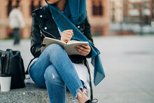 Crop Muslim Female In Hijab Writing In Diary While Sitting On City Street And Looking Away