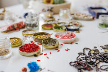 Side View Of Various Decorative Bugle Beads In Metal Containers On Wooden Table