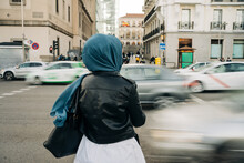 Back View Of Anonymous Muslim Female In Hijab Standing Near Road With Busy Traffic In Rush Hour