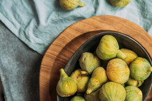 Fresh And Ripe Sweet Green Figs, In A Black Bowl On The Wood Plate Served On The Blue Tablecloth Table, Seasonal Organic Fruit. Also Known As Ripe White Figs
