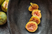 Green Fig Slices In Modern Black Bowl On The Table With Grunge Texture. Minimal Concept Food. Also Known As Ripe White Figs