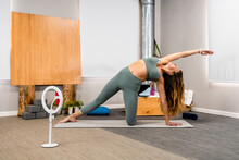 Full Length Of Fit Young Woman Performing Side Plank On The Knee With Arm Extended Asana While Practicing Yoga On Man In Modern Apartment Near Smartphone On Tripod