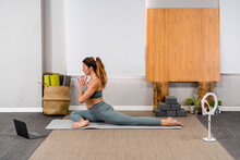 Side View Of Calm Young Lady In Activewear Performing Half Pigeon Yoga Pose With Prayer Hands During Online Training At Home Near Laptop And Tripod With Smartphone